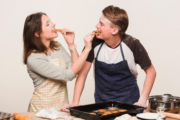 Paare, die zusammen kochen und gebäck schmecken