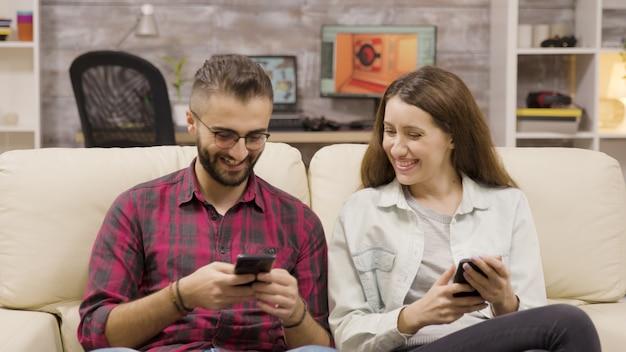 Paare, die zusammen lachen, während sie auf ihren telefonen surfen. paar sitzt auf der couch.