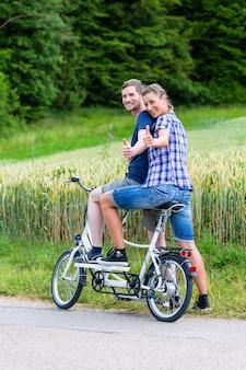 Paare, die zusammen tandemfahrrad im land reiten