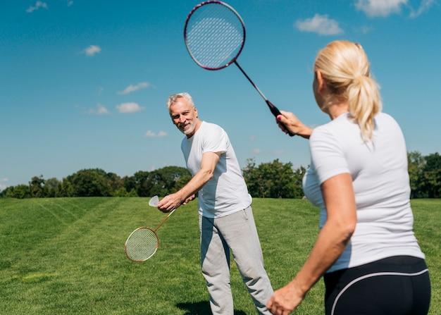 Paare, die zusammen tennis draußen spielen