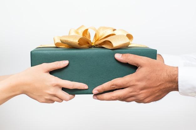 Paare, die zusammen verpacktes weihnachtsgeschenk halten