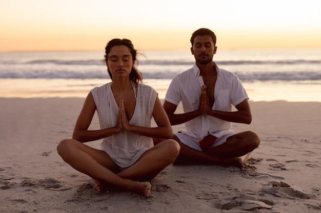 Paare, die zusammen yoga auf dem strand durchführen
