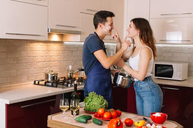 Paare, die zusammen zu hause in der küche kochen
