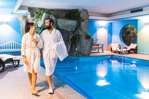 Paare entspannen herein sich an der therme, am badekurort mit swimmingpool