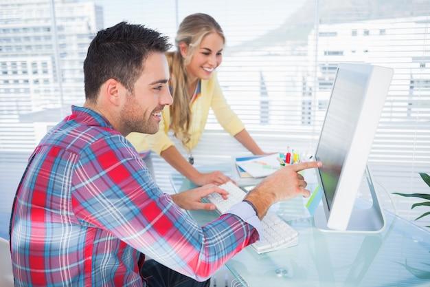 Paare fotoredakteure, die zusammen an einem computer arbeiten