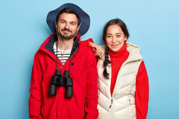 Paare haben eine gemeinsame reise, stehen eng beieinander, tragen hut und freizeitkleidung, erkunden mit einem fernglas einen neuen ort