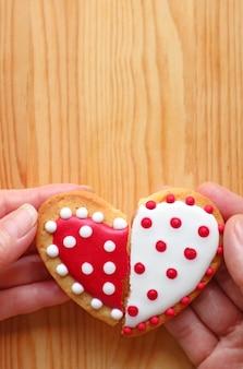 Paare hände, die zwei halbherzförmige kekse halten, befestigen auf hölzernem hintergrund