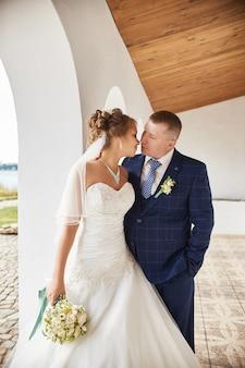 Paare heiraten umarmung und küssen häuser nahe wasser
