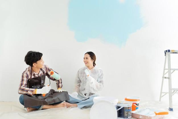 Paare helfen, das neue haus zu malen