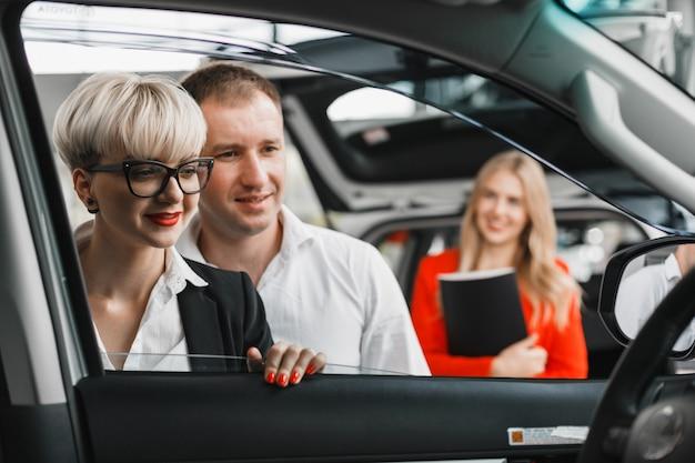Paare im autohaus wählen ein auto omage