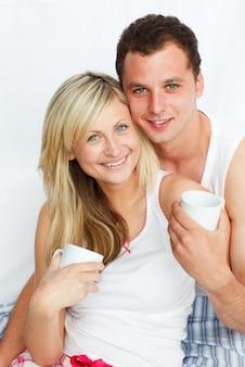 Paare im bett kaffee trinkend und an der kamera lächelnd