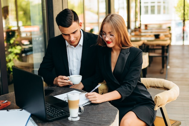 Paare im café, das am laptop während des abendessens arbeitet. - bild