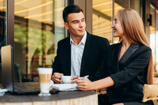 Paare im café, das am laptop während des abendessens arbeitet und sich schaut. - bild