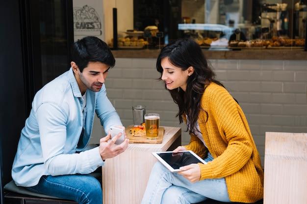 Paare im café, das smartphoneschirm betrachtet