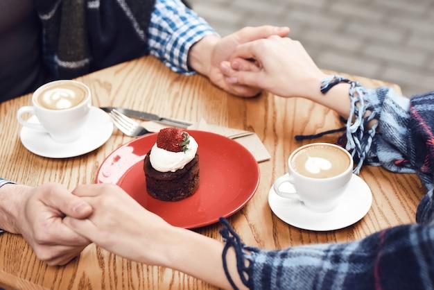 Paare im händchenhalten lieben cappuccino-kleinen kuchen.