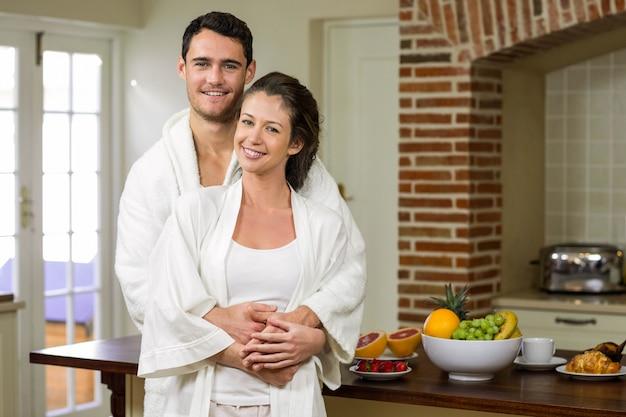 Paare im lächelnden bademantel bei der umfassung in der küche