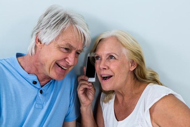 Paare im ruhestand, die musik durch smartphone hören