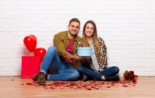Paare im valentinstag an einem geschenk in den händen zuhause halten