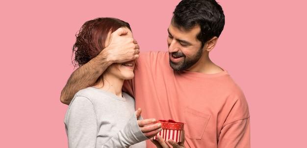 Paare im valentinstag, der geschenkbox über lokalisiertem rosa hintergrund hält
