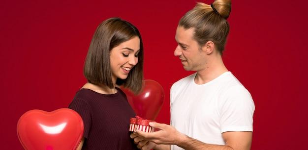 Paare im valentinstag, der geschenkbox über rotem hintergrund hält