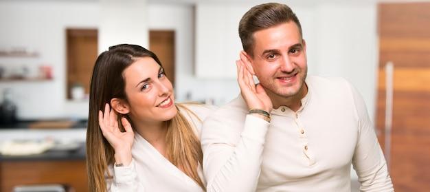 Paare im valentinstag hörend etwas in einem haus