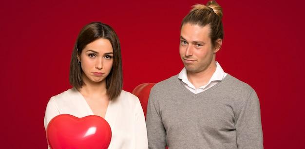 Paare im valentinstag mit traurigem und deprimiertem ausdruck über rotem hintergrund