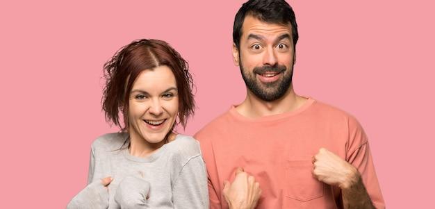 Paare im valentinstag mit überraschungsgesichtsausdruck über lokalisiertem rosa hintergrund