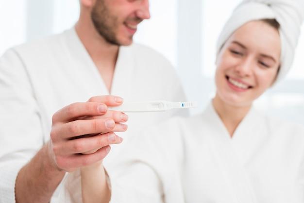 Paare in den bademäntel, die schwangerschaftstest halten
