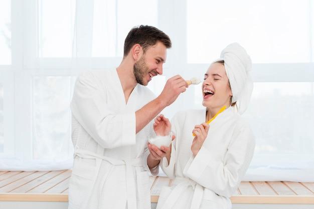 Paare in den bademänteln, die mit rasierschaum herumalbern