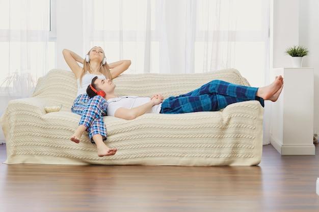 Paare in den kopfhörern, die auf dem sofa hört musik im raum liegen