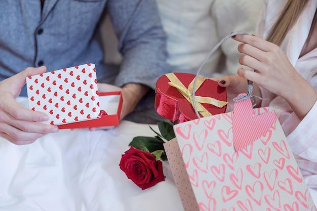 Paare in den pyjamas, die auf bett mit geschenken sitzen