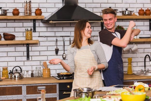 Paare in den schürzen, die spaß haben und in küche tanzen