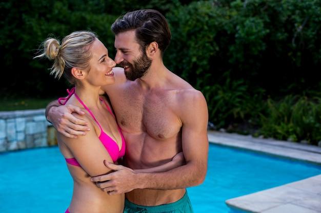 Paare in der badebekleidung, die sich umfasst