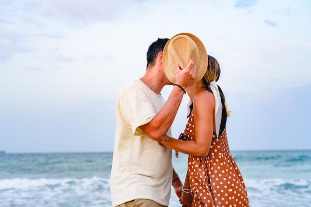 Paare in der liebe, die auf das ufer des strandes spielt und geht.
