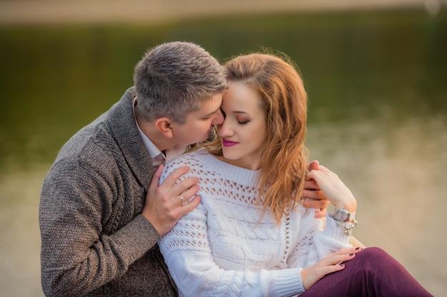 Paare in der liebe, die auf dem see im herbst umarmt