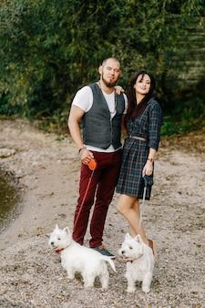 Paare in der liebe, die auf dem strand mit weißen hunden stillsteht