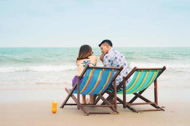 Paare in der liebe, die auf den strandstühlen auf tropischem strand in den sommerferien sitzt