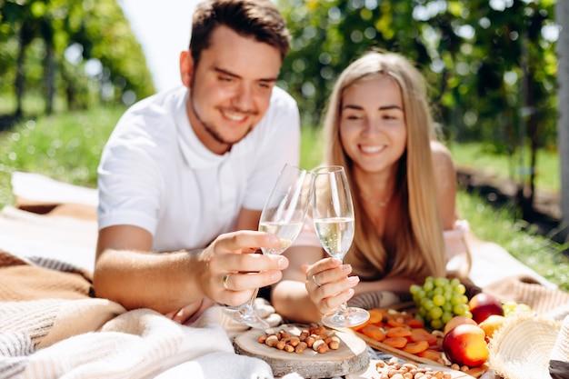Paare in der liebe, die auf einer picknickdecke liegt, gläser wein hält und einen toast macht