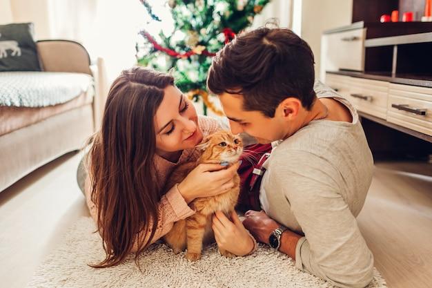 Paare in der liebe, die durch weihnachtsbaum liegt und zu hause mit katze spielt. mann und frau entspannen
