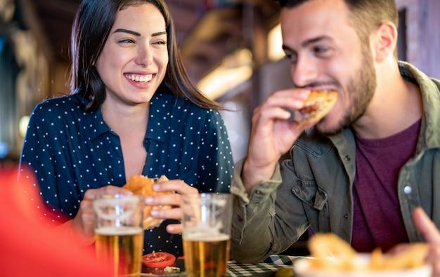 Paare in der liebe, die spaß hat, burger an der restaurantkneipe zu essen