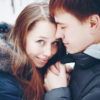Paare in der liebe, die spaß im winterwald umarmt und hat