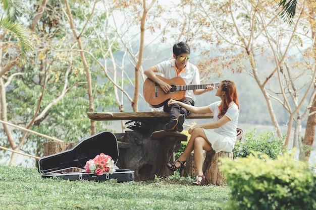 Paare in der liebe mit dem spielen der gitarre an der natur