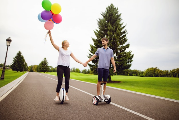 Paare in der liebe, welche die straßenhändchenhalten reitet.
