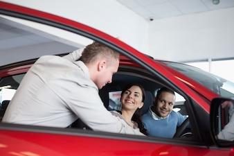 Paare in einem Auto hörend auf einen Verkäufer