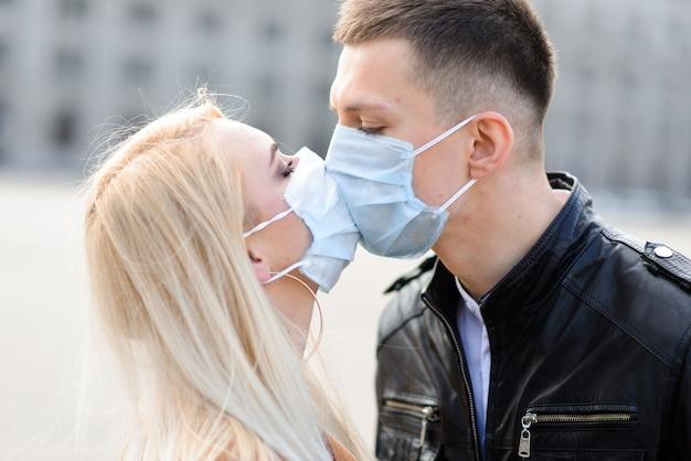 Paare in schutzmasken machen zur quarantänezeit einen spaziergang im freien in der stadt in der nähe des geschäftsgebäudes. konzeption des coronavirus.