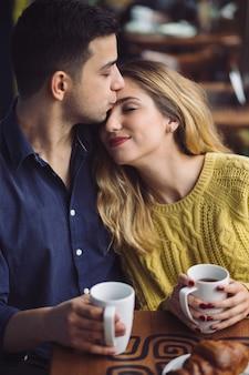 Paare in trinkendem kaffee der liebe in der kaffeestube
