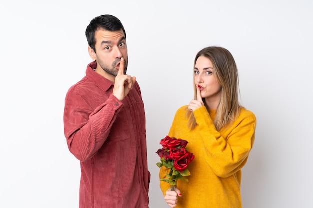 Paare in valentine day, der blumen über der lokalisierten wand zeigt ein zeichen des schließenden munds und der ruhegeste hält