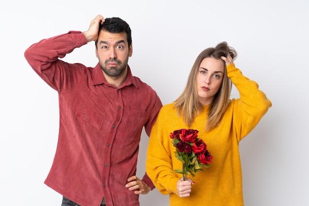 Paare in valentine day, der blumen über lokalisierter wand mit einem ausdruck der frustration und des nichtverständnisses hält