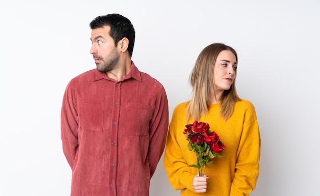 Paare in valentine day, der blumen über lokalisierter wand nervös und erschrocken hält
