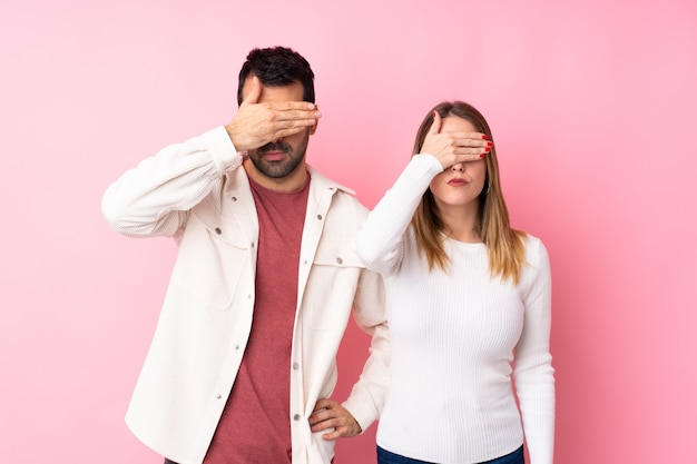Paare in valentine day über lokalisierten rosa wandverkleidungsaugen durch hände. ich will nichts sehen